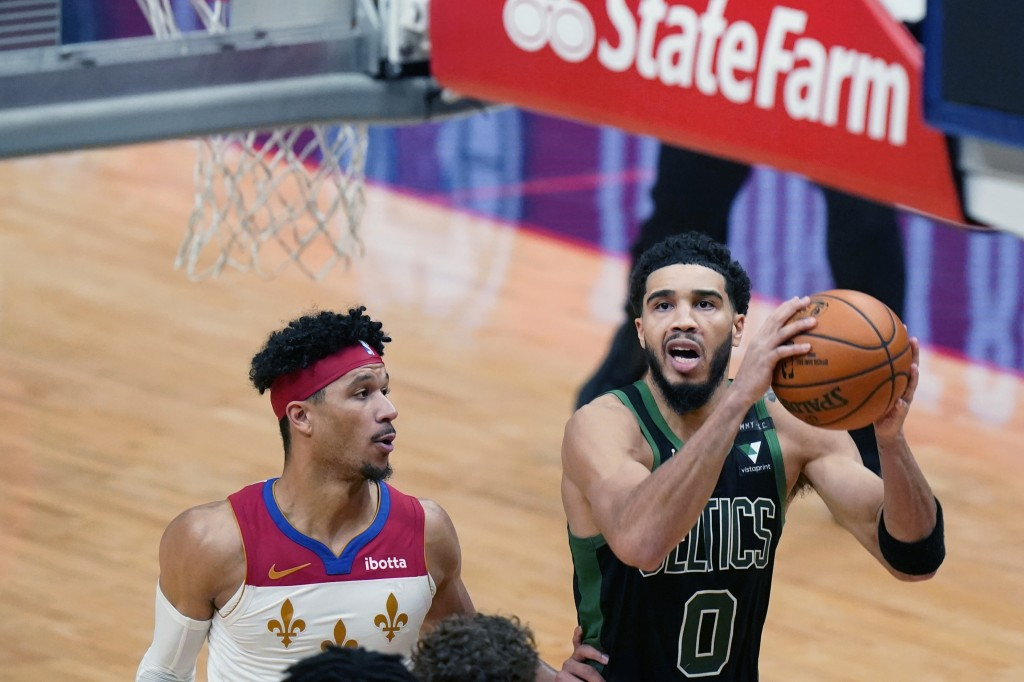 Boston Celtics forward Jayson Tatum (0) drives to the basket past New Orleans Pelicans guard Josh Hart to score the tying points in the second half of...