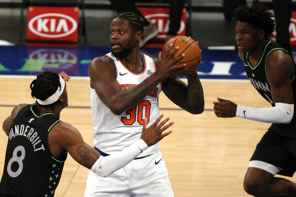 Julius Randle, center, of the New York Knicks looks to pass as Jarred Vanderbilt, left, and Anthony Edwards, right, of the Minnesota Timberwolves defe...