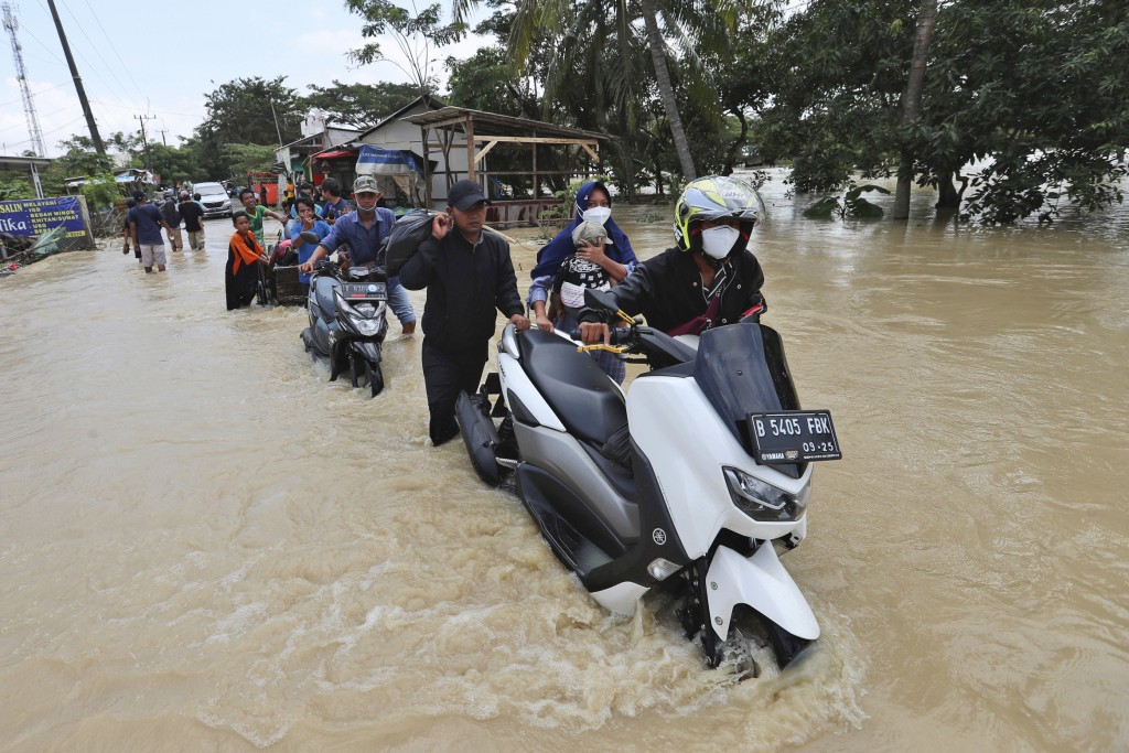 People push their motorcycles through a flooded area after the embankment of Citarum River burst, in Bekasi, Indonesia, Monday, Feb. 22, 2021. Heavy r...