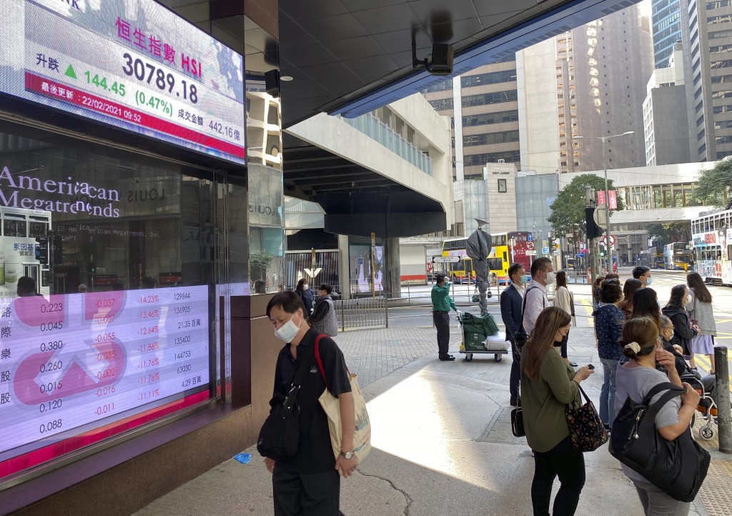 People walk past a bank's electronic board showing the Hong Kong share index in Hong Kong Monday, Feb. 22, 2021. Asian shares were mixed on Monday as ...
