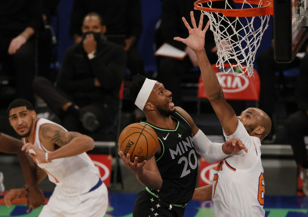 Josh Okogie, center, of the Minnesota Timberwolves shoots as Taj Gibson, right, and Obi Toppin, left, of the New York Knicks defend during the first h...