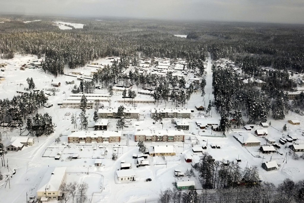 Snow coats the village of Ikhala in Russia's Karelia region, Tuesday, Feb. 16, 2021. The village of wooden houses — carved out of a dense forest of fi...