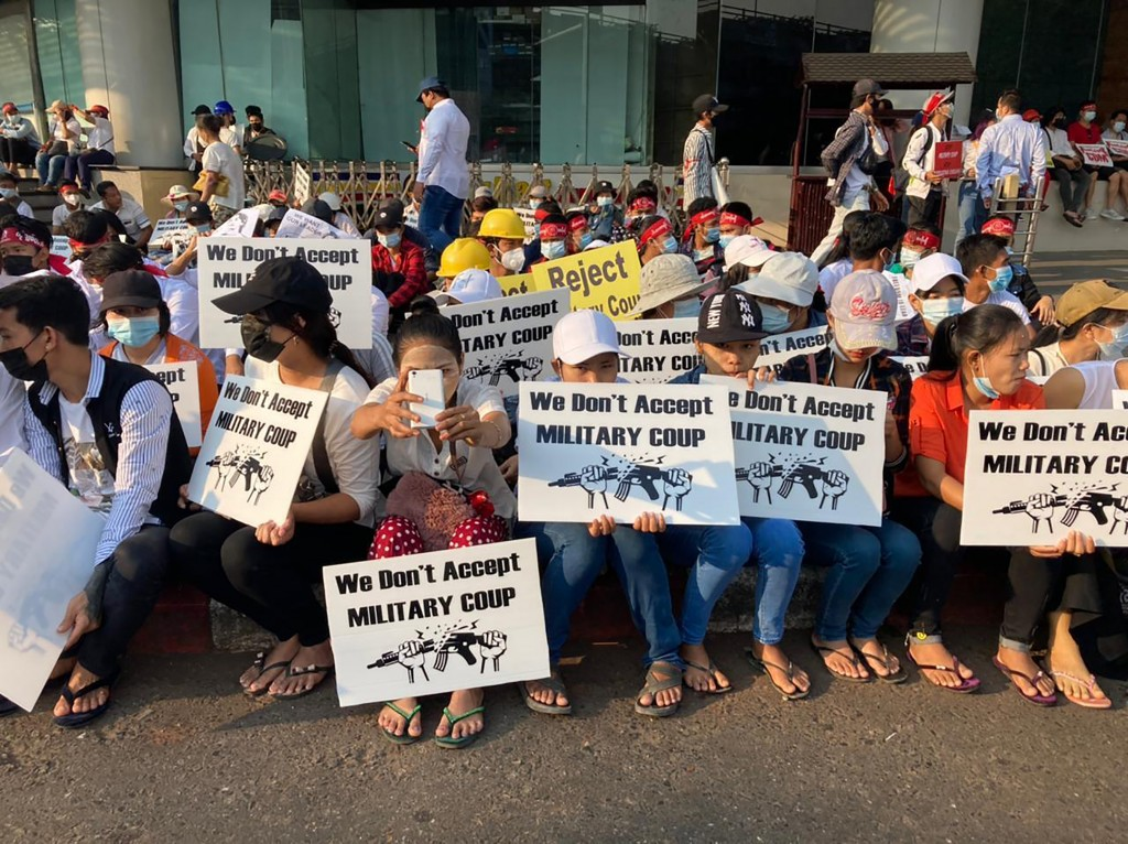 """Anti-coup protesters hold signs that read """"We Don't Accept Military Coup"""" as they gather outside the Hledan Centre in Yangon, Myanmar Monday, Feb. 22,..."""