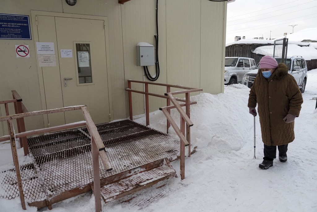 An elderly woman walks to a local rural medical post to get a Sputnik V vaccine in the village of Ikhala in Russia's Karelia region, Tuesday, Feb. 16,...