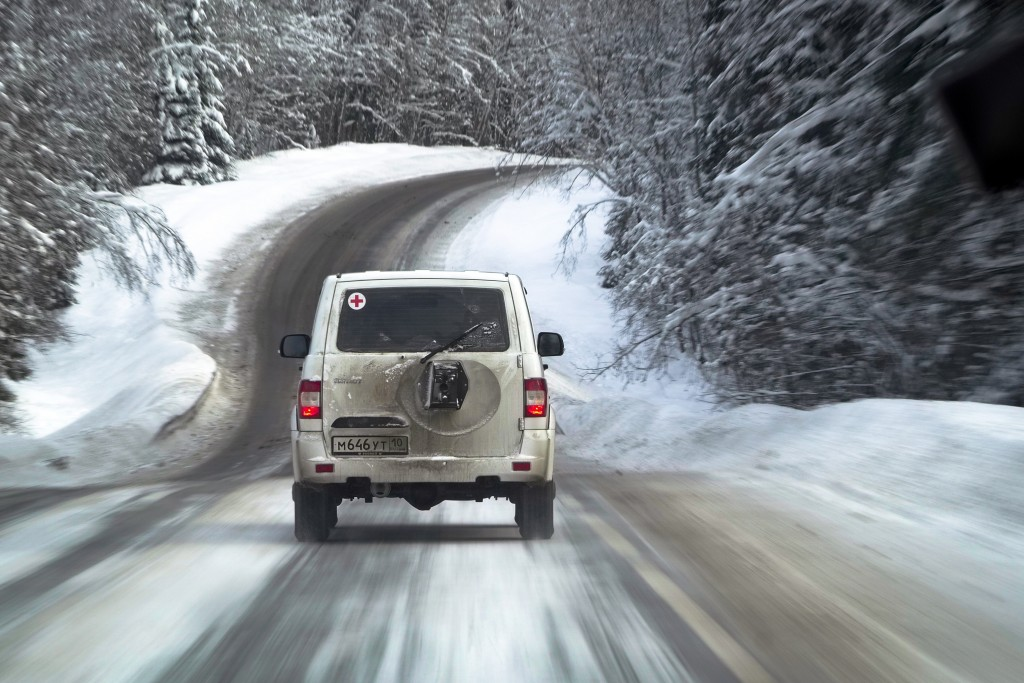A medical car moves along a snowy road carrying COVID-19 vaccines heading to the village of Ikhala in Russia's Karelia region, Tuesday, Feb. 16, 2021....