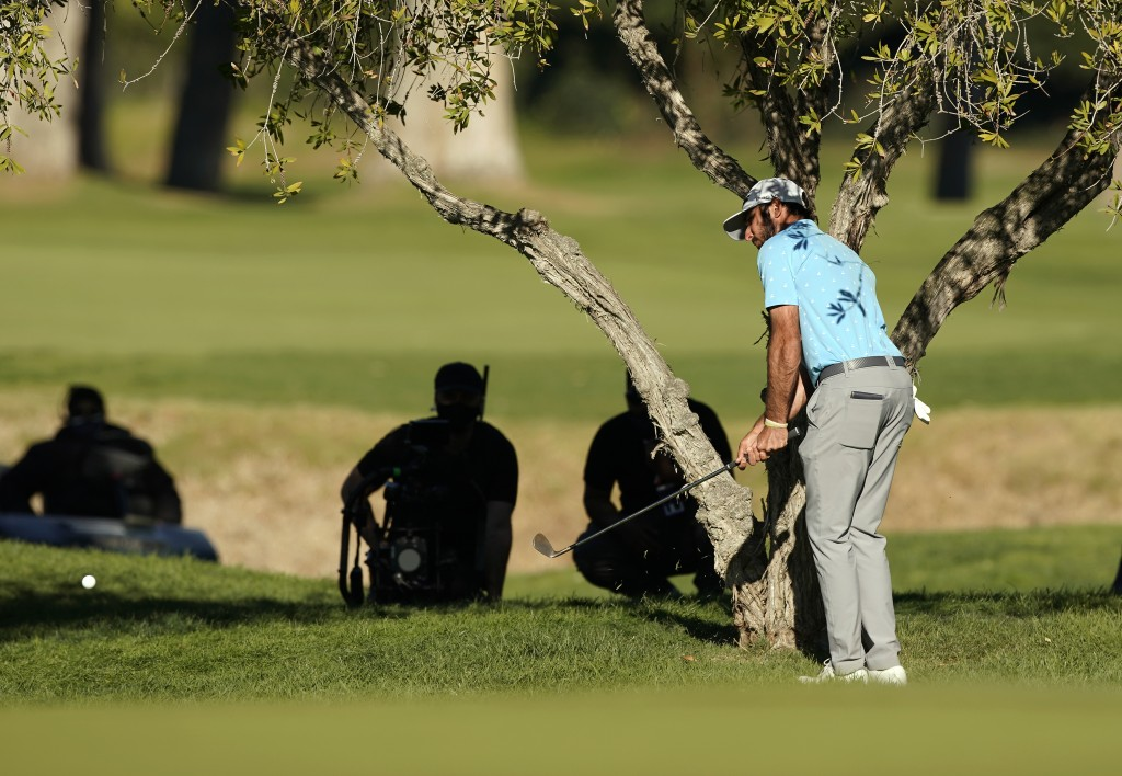 Max Homa hits his second shot from under a tree on the 10th hole during a playoff against Tony Finau in the final round of the Genesis Invitational go...