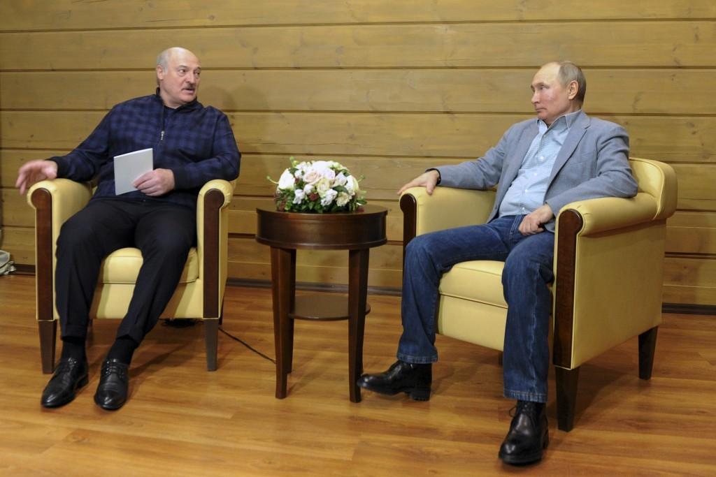 Russian President Vladimir Putin, right, listens to Belarusian President Alexander Lukashenko during their meeting in the Black Sea resort of Sochi, R...