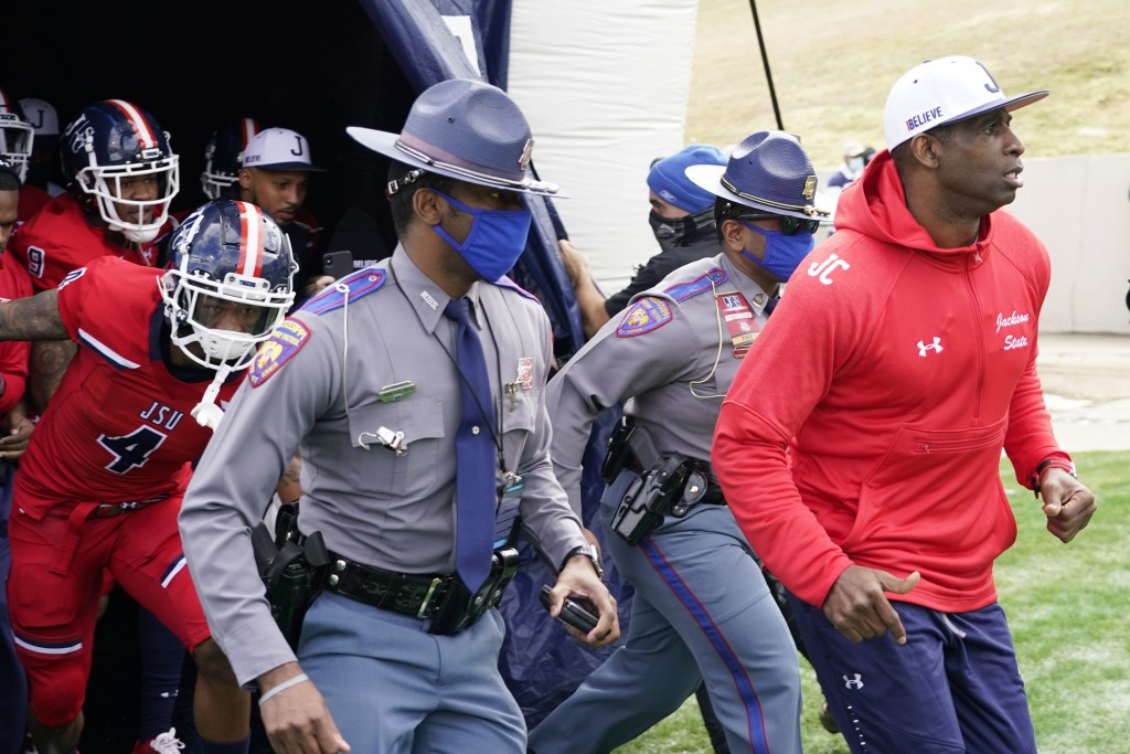 Jackson State football coach Deion Sanders, right, leads an accompanying security detail and his team onto the field prior to the first half of an NCA...