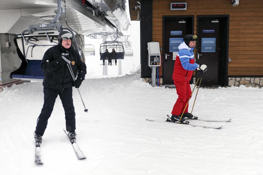 Russian President Vladimir Putin, right, and Belarusian President Alexander Lukashenko arrive at the mountain resort of Krasnaya Polyana near the Blac...