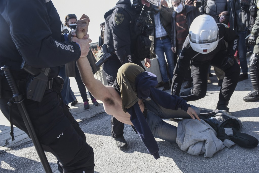 Police detain a protester at the University of Thessaloniki in northern Greece, on Monday, Feb. 22, 2021. Police clashed with protesters and detained ...
