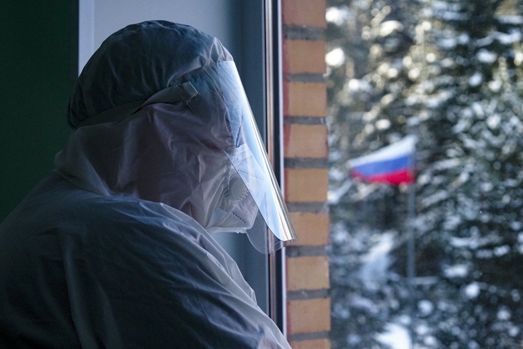 Alexander Romanov, chief physician of the hospital in Sortavala wearing protective gear looks through a window of a local rural medical post in the vi...