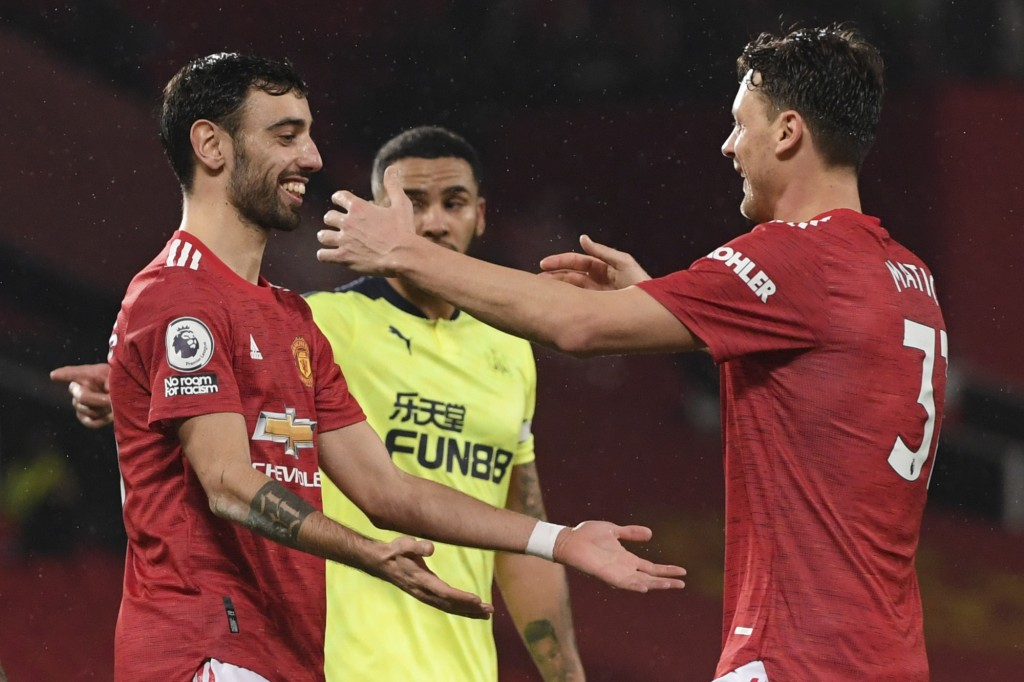 Manchester United's Bruno Fernandes, left, celebrates with Nemanja Matic after scoring his side's third goal from the penalty spot during an English P...