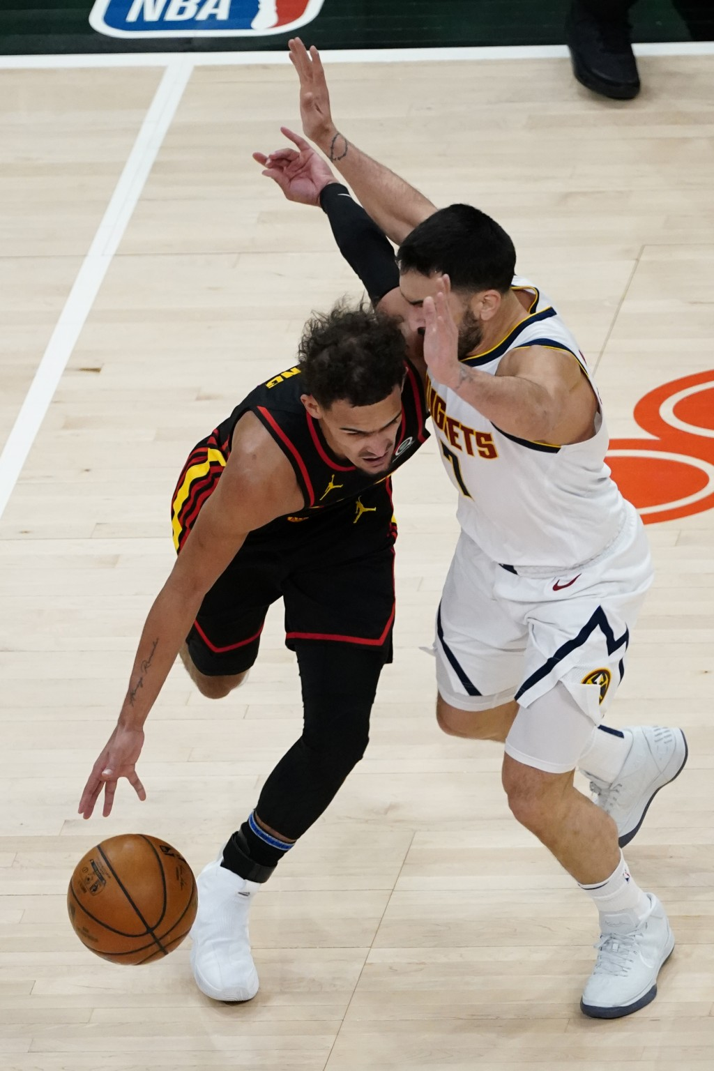 Atlanta Hawks guard Trae Young, left, drives against Denver Nuggets guard Facundo Campazzo, right, during the second half of an NBA basketball game Su...
