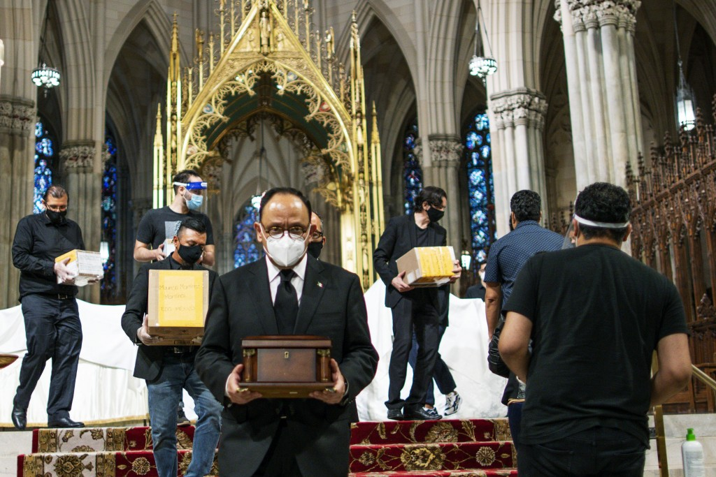 Jorge Islas Lopez, Consul General of Mexico, and others carry the remains of loved ones following the blessing of the ashes of Mexicans who died from ...