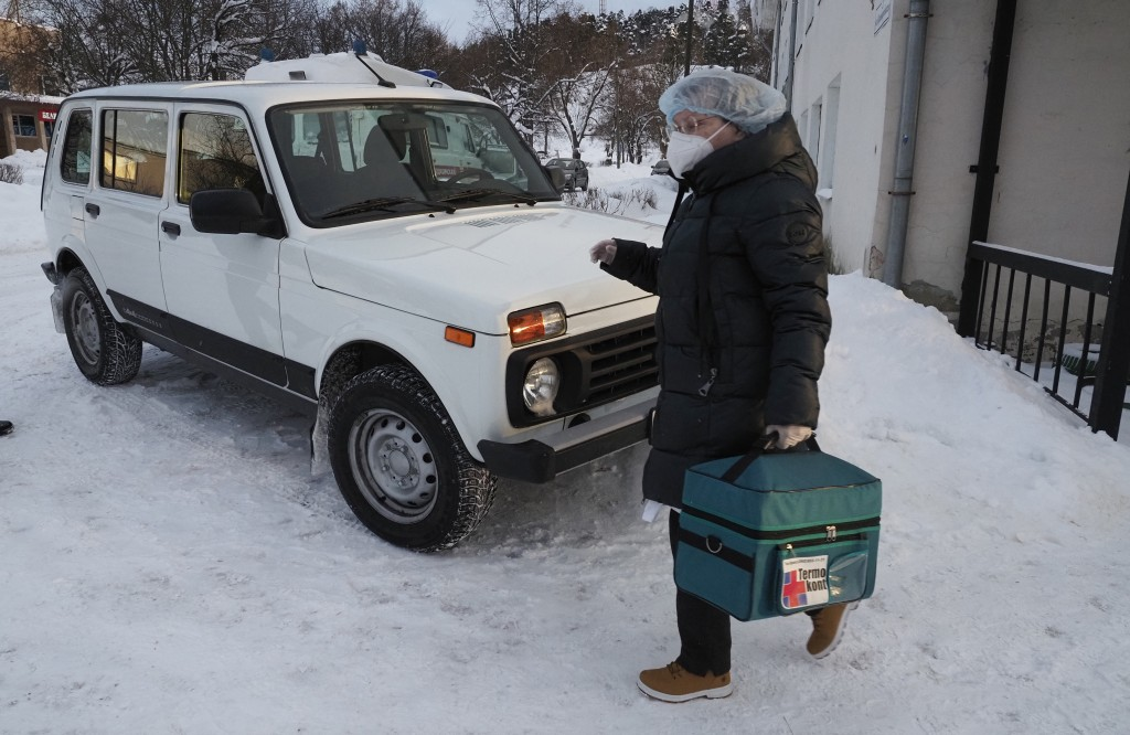 A medical worker carries a thermal bag with vaccines from a clinic in Lakhdenpokhya to drive to Ikhala, one of several remote villages in the village ...