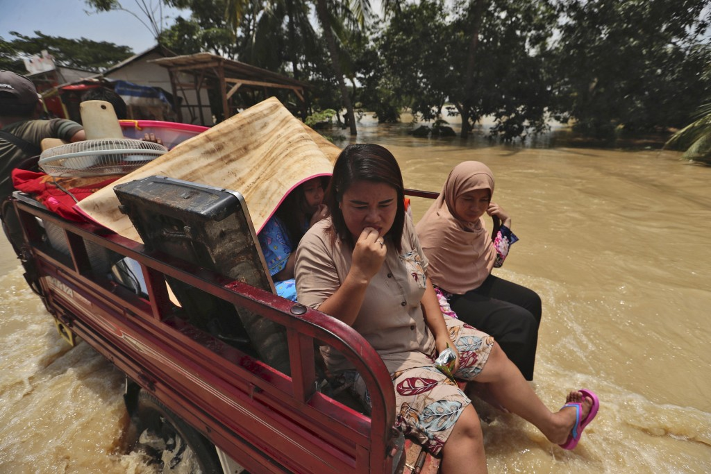 Indonesian women sit on the back of a three-wheeled motorcycle carrying their belongings to high ground at an area flooded after the embankment of Cit...
