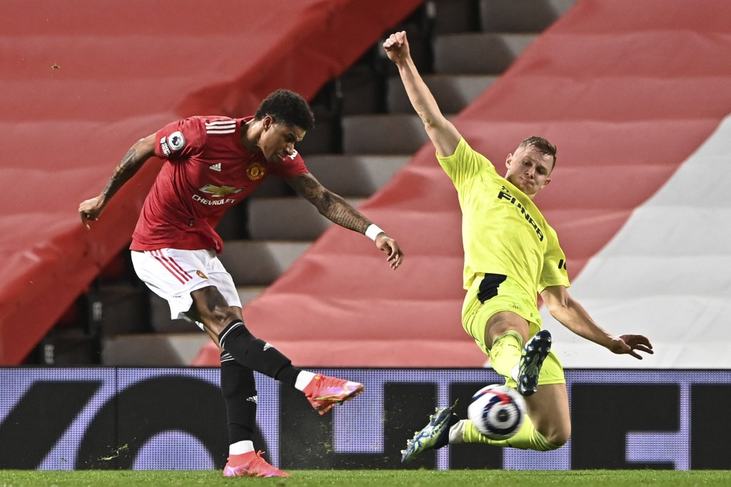 Manchester United's Marcus Rashford, left, shoots to score the opening goal during an English Premier League soccer match between Manchester United an...