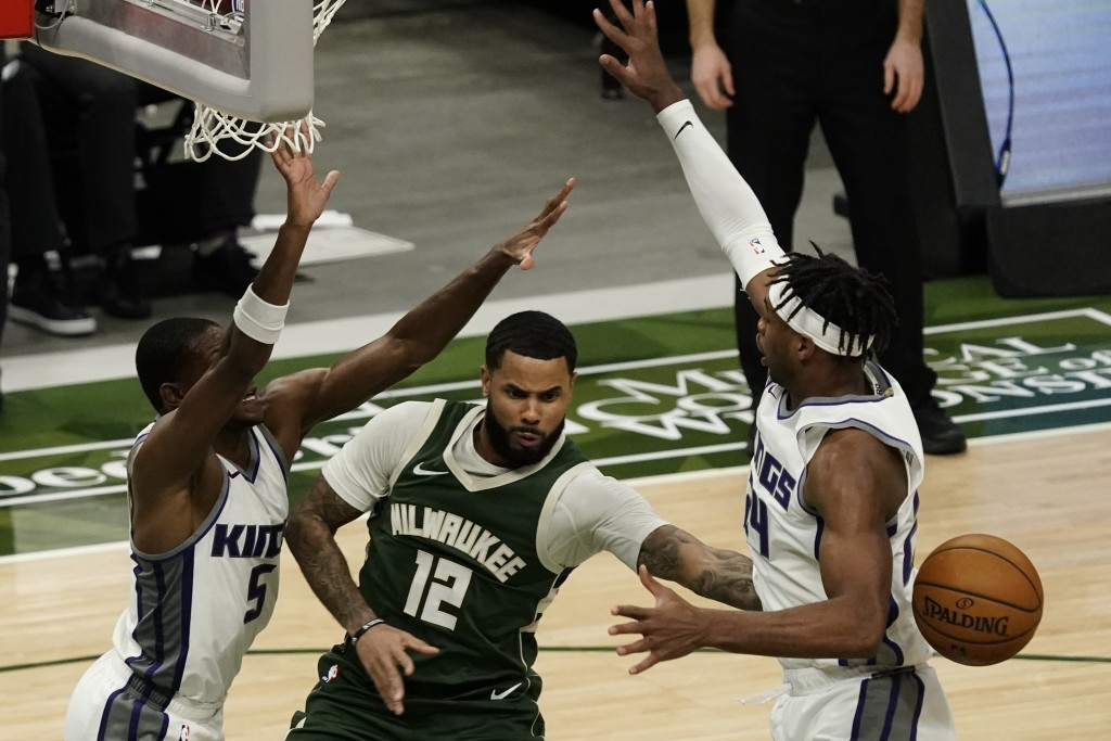 Milwaukee Bucks' D.J. Augustin passes around Sacramento Kings' Buddy Hield during the second half of an NBA basketball game Sunday, Feb. 21, 2021, in ...