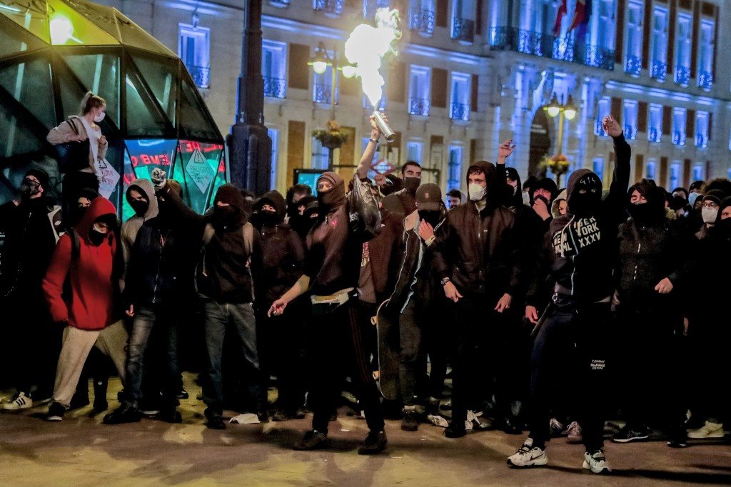 Demonstrators react during clashes as they protest against the arrest of rap artist Pablo Hasel in Madrid, Spain, Wednesday, Feb. 17, 2021. The impris...