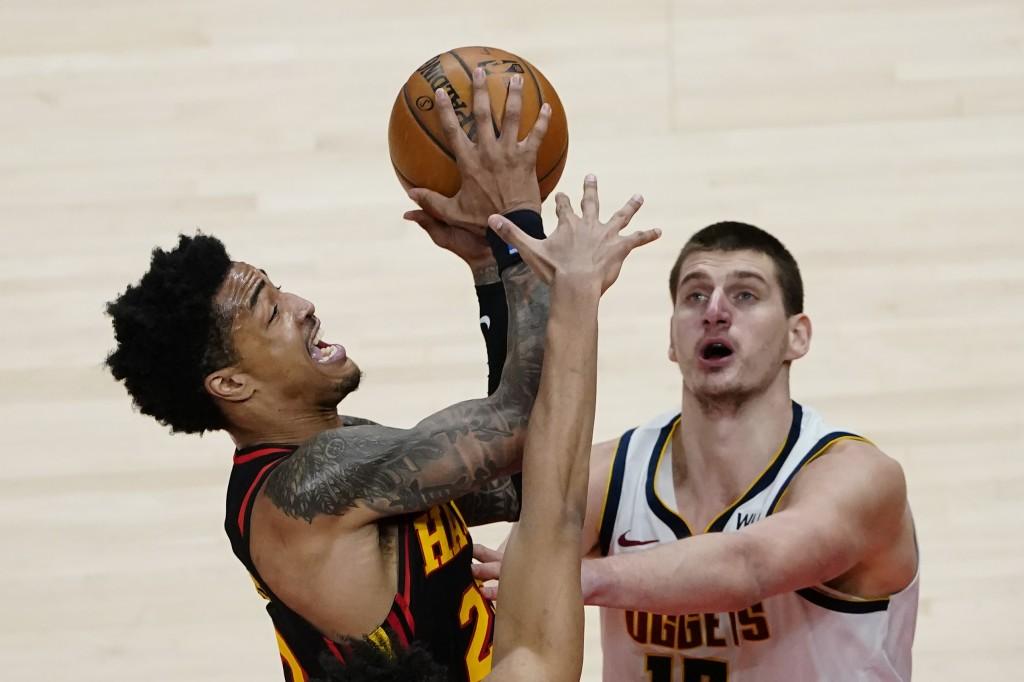 Atlanta Hawks forward John Collins, left,  goes in for a basket as Denver Nuggets center Nikola Jokic, right,  defends during the second half of an NB...