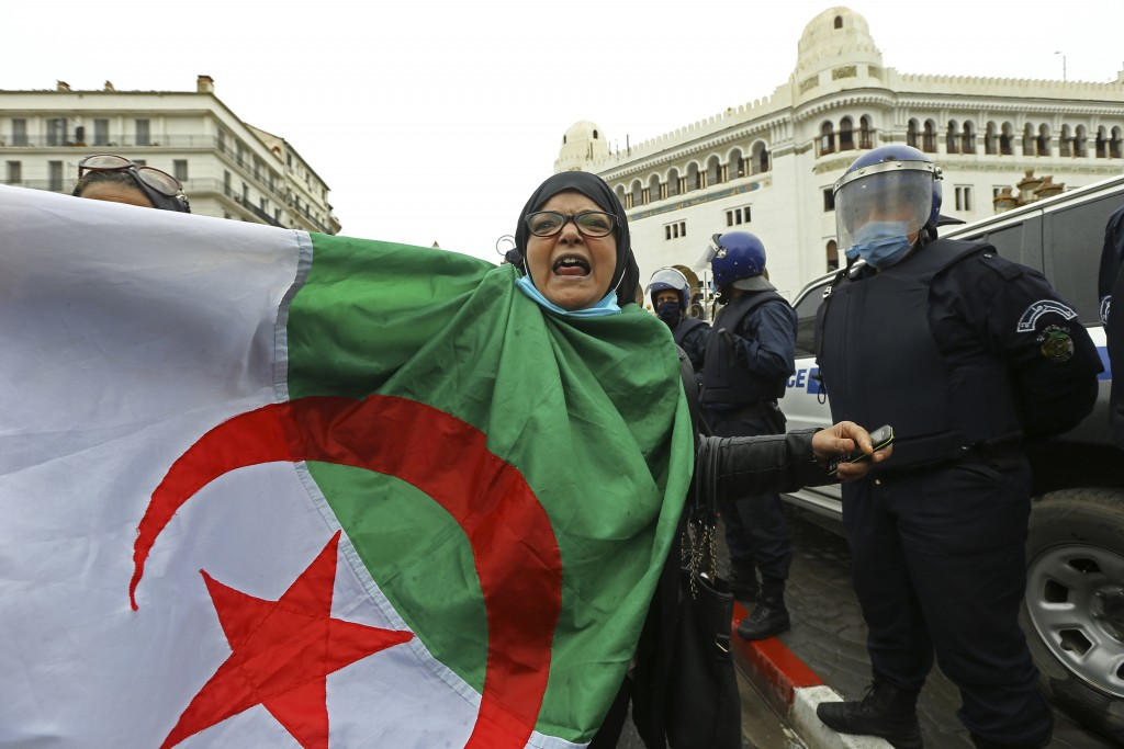 A woman holds an Algerian flag as Algerians demonstrate in Algiers to mark the second anniversary of the Hirak movement, Monday Feb. 22, 2021. Februar...