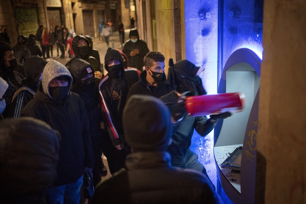 Demonstrators use an extinguisher to destroy a cash machine during a protest condemning the arrest of rap artist Pablo Hasél in Barcelona, Spain, Frid...
