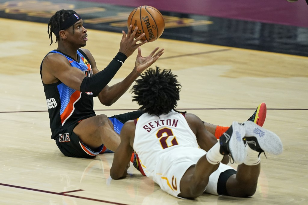 Oklahoma City Thunder's Shai Gilgeous-Alexander, left, passes the ball as Cleveland Cavaliers' Collin Sexton watches in the first half of an NBA baske...