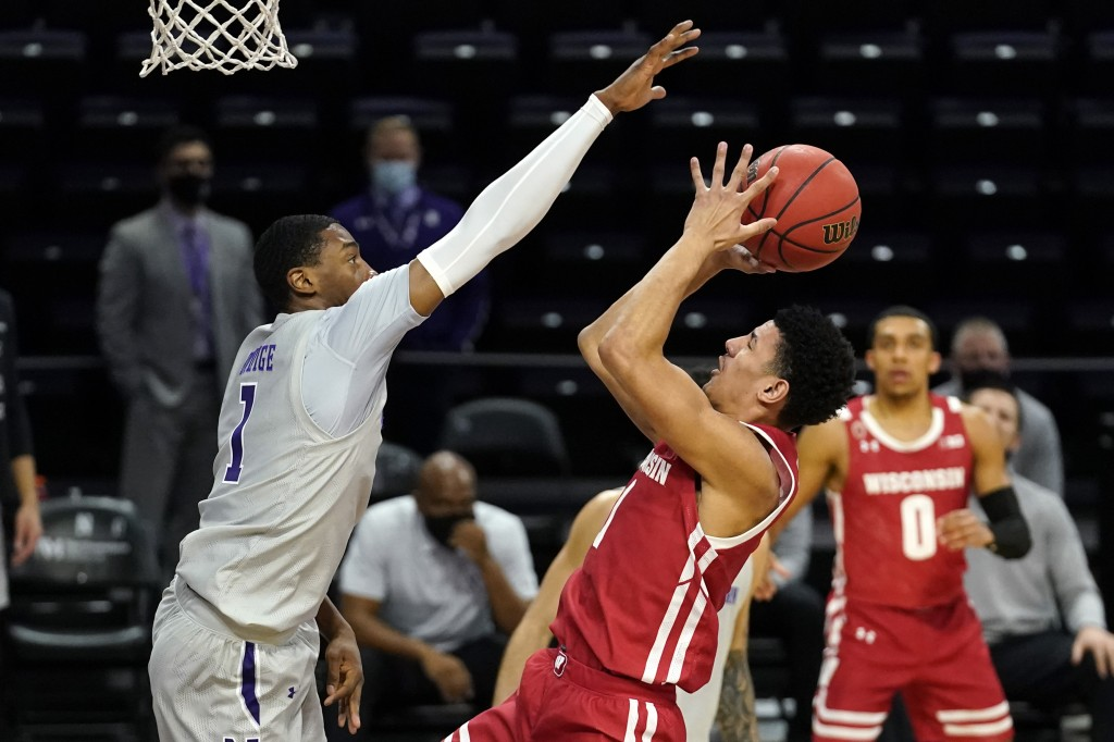 Wisconsin guard Jonathan Davis, right, shoots against Northwestern guard Chase Audige during the first half of an NCAA college basketball game in Evan...