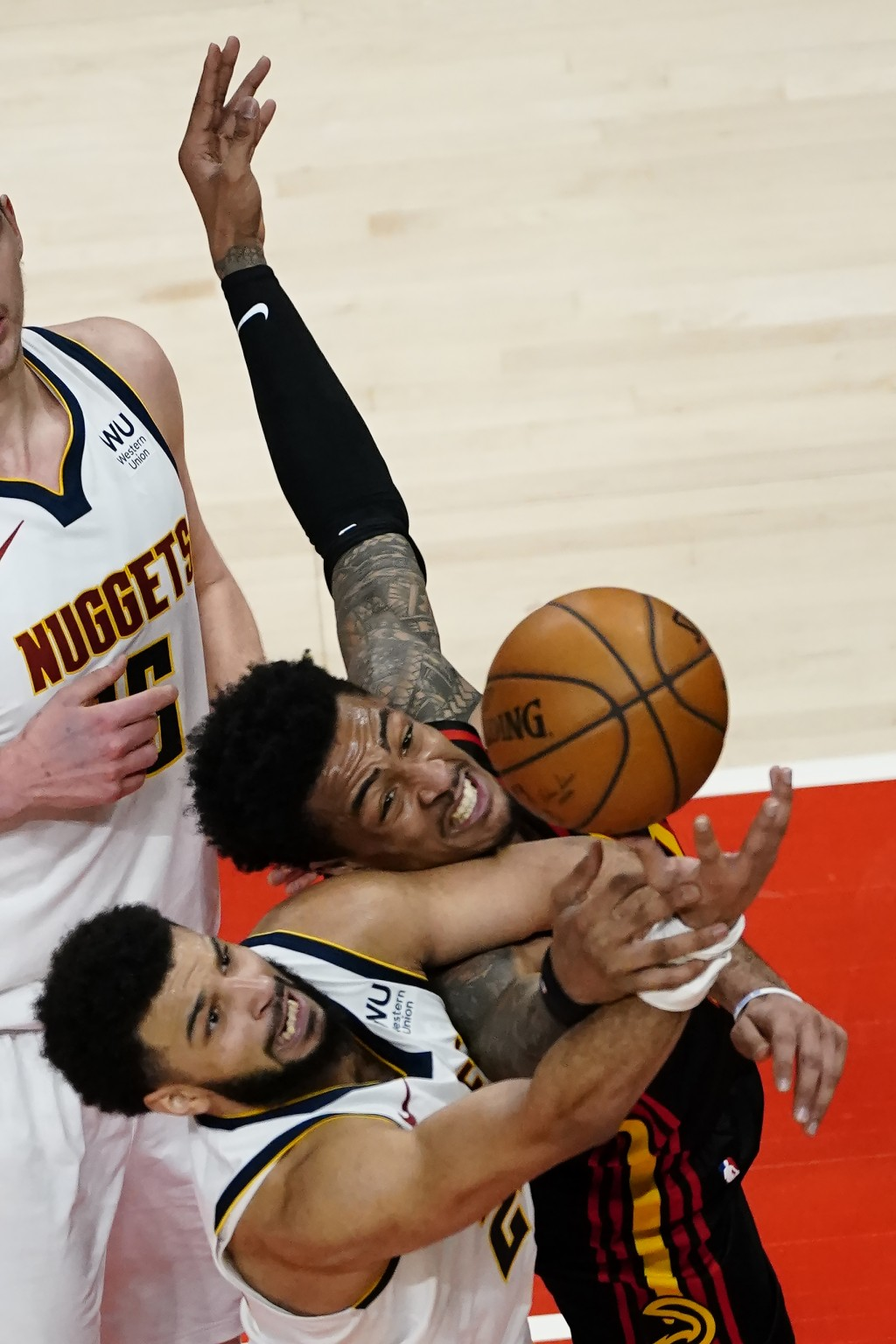 Denver Nuggets guard Jamal Murray, bottom, and Atlanta Hawks forward John Collins vie for a rebound during the second half of an NBA basketball game S...