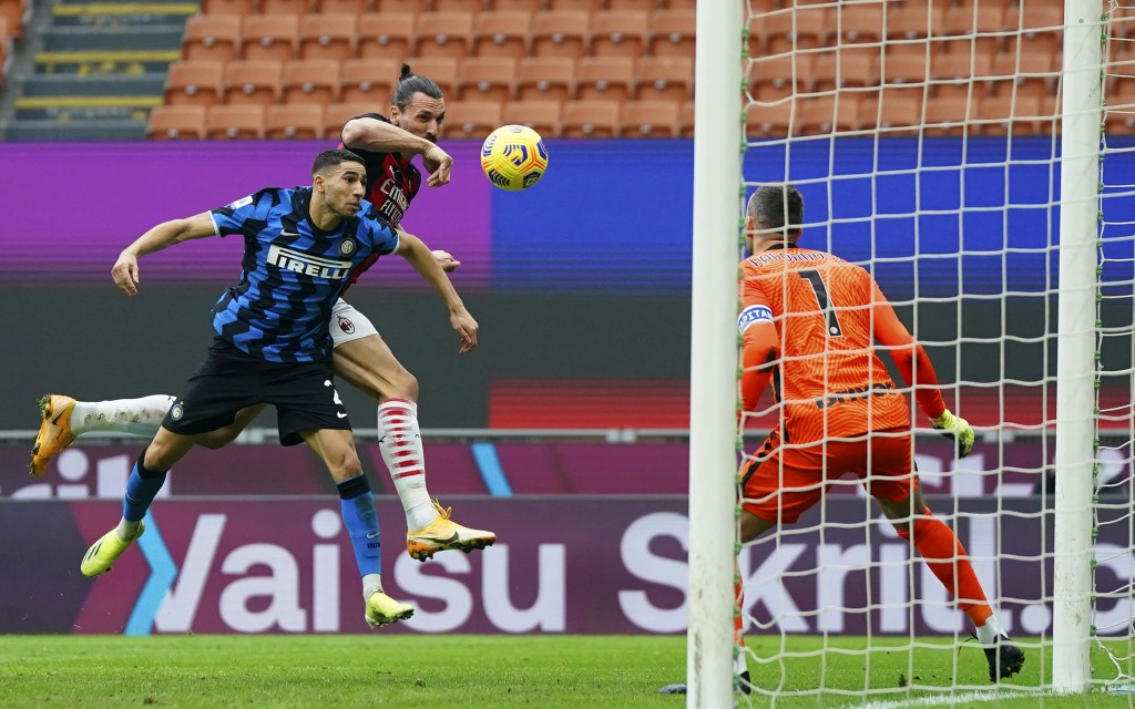 AC Milan's Zlatan Ibrahimovic, top, and Inter's Hakimi vie for the ball during the Serie A soccer match between AC Milan and Inter Milan, at the San S...