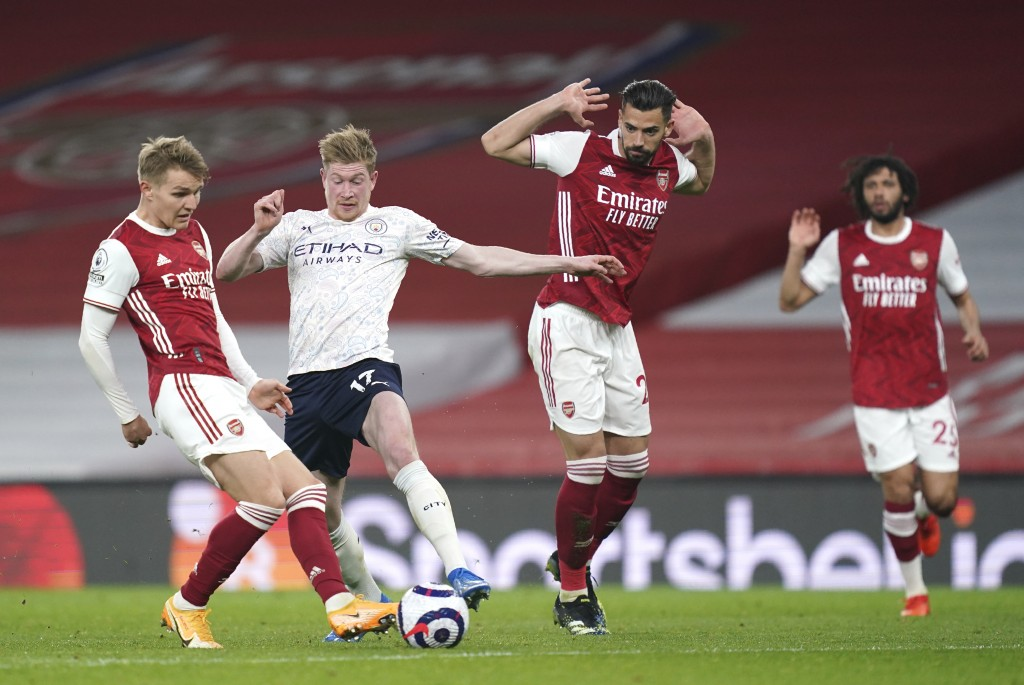 Arsenal's Martin Odegaard, left, and Manchester City's Kevin De Bruyne challenge for the ball during the English Premier League soccer match between A...