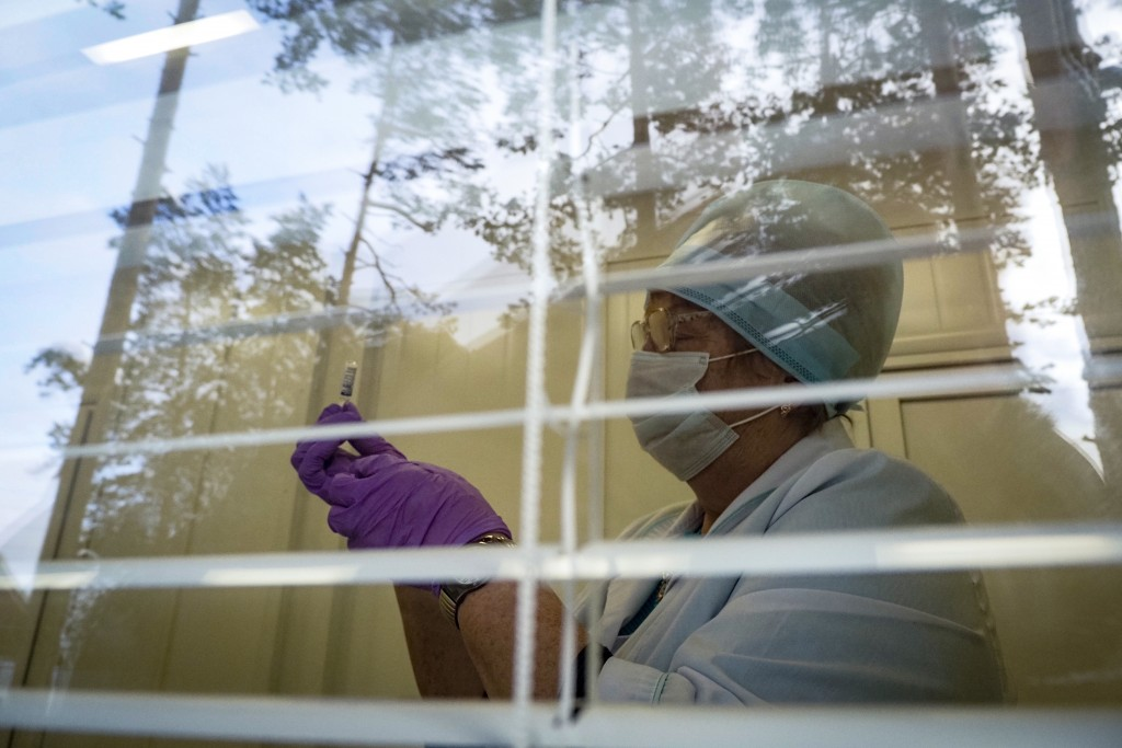 A medical worker preparing a shot of Russia's Sputnik V coronavirus vaccine is seen through a window of a local rural medical post in the village of I...
