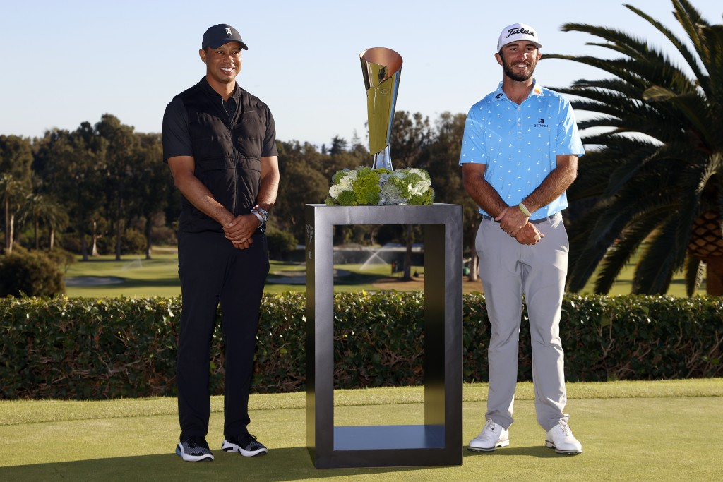 Max Homa, right, poses with his trophy next to Tiger Woods on the practice green after winning the Genesis Invitational golf tournament at Riviera Cou...