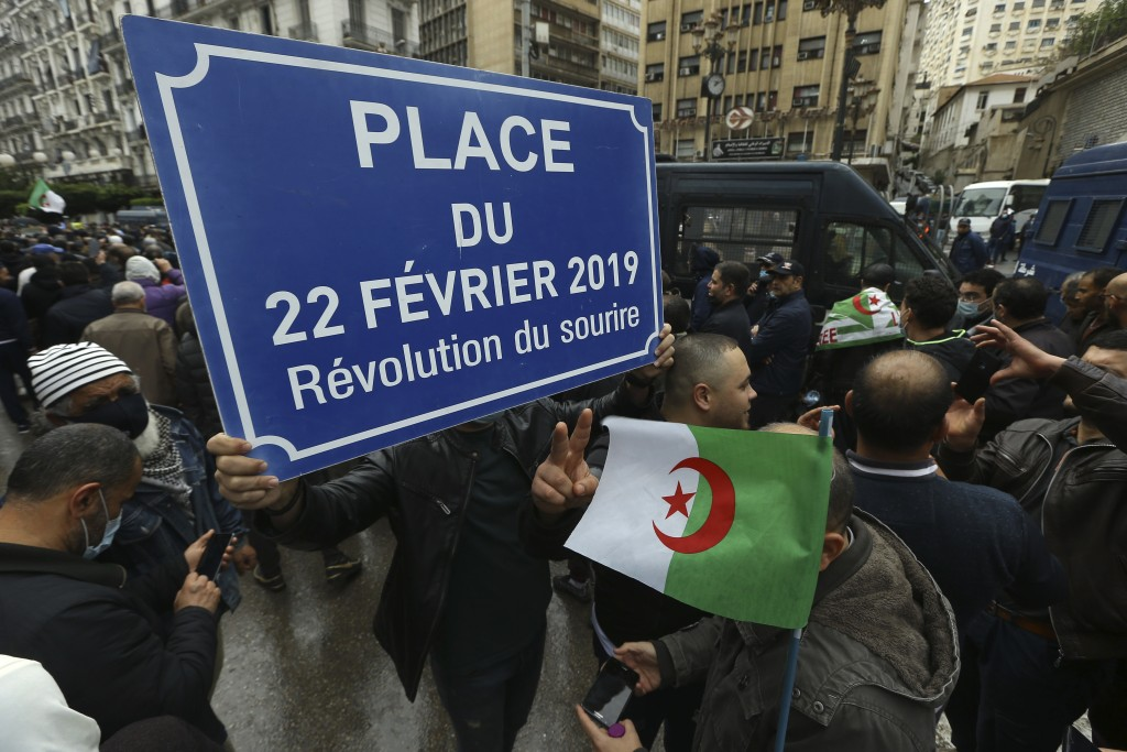 "Algerians demonstrate in Algiers, one with a plaque reading ""Square of Feb.22, 2019, the Smiling Revolution"" to mark the second anniversary of the Hir..."