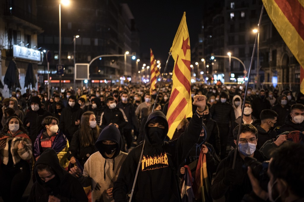 People march during a protest condemning the arrest of rap artist Pablo Hasél in Barcelona, Spain, Friday, Feb. 19, 2021. The imprisonment of a rap ar...