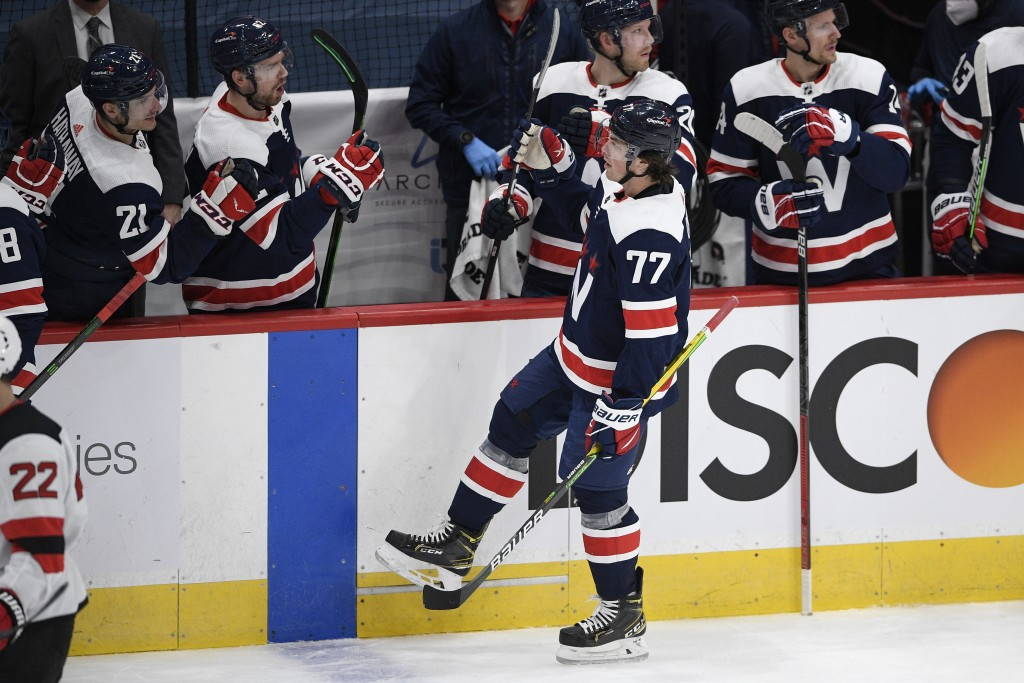 Washington Capitals right wing T.J. Oshie (77) celebrates his goal with the bench during the second period of an NHL hockey game against the New Jerse...
