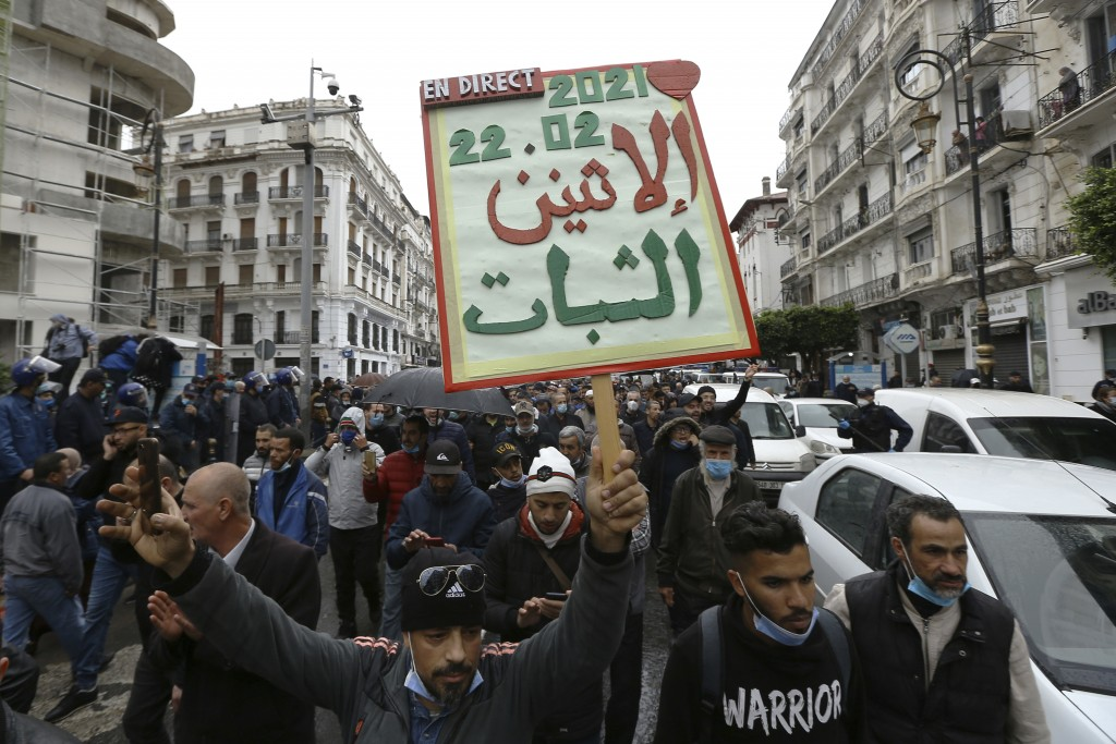 "Algerians demonstrate, one with a poster reading ""Resistance Monday"" in Algiers as they mark the second anniversary of the Hirak movement, Monday Feb...."