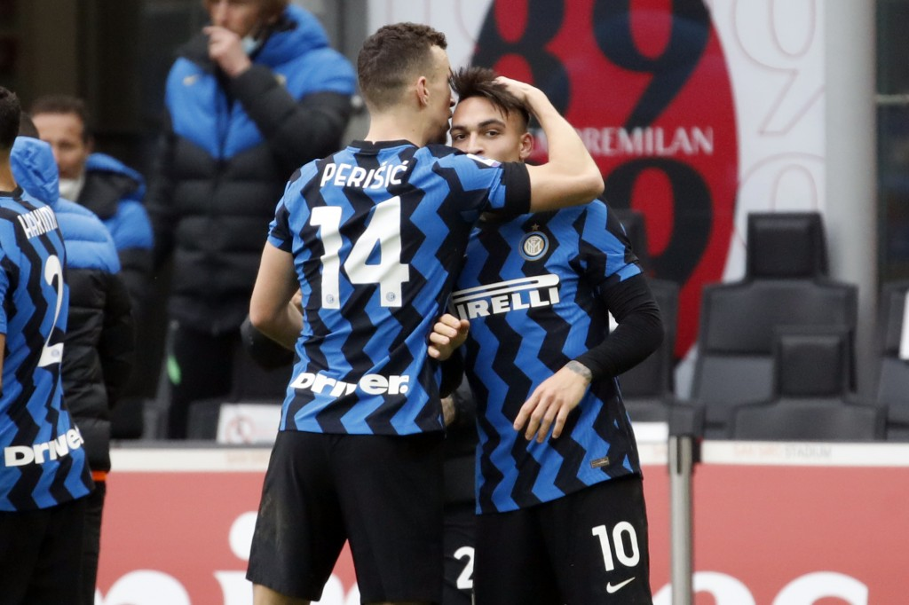 Inter Milan's Lautaro Martinez, right, celebrates with Ivan Perisic after scoring his side's second goal during the Serie A soccer match between AC Mi...