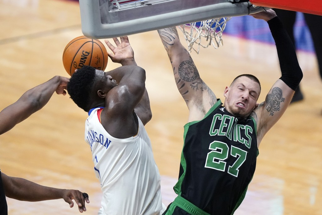 New Orleans Pelicans forward Zion Williamson is stripped of the ball as he drives to the basket against Boston Celtics center Daniel Theis (27) in the...