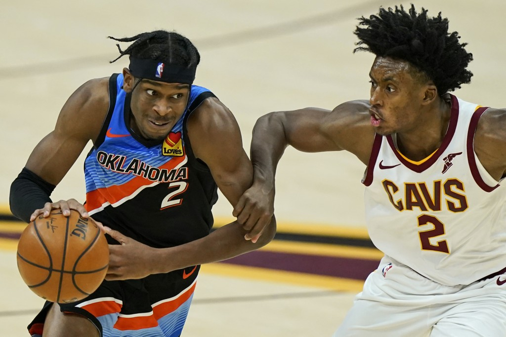 Oklahoma City Thunder's Shai Gilgeous-Alexander, left, drives past Cleveland Cavaliers' Collin Sexton in the second half of an NBA basketball game, Su...