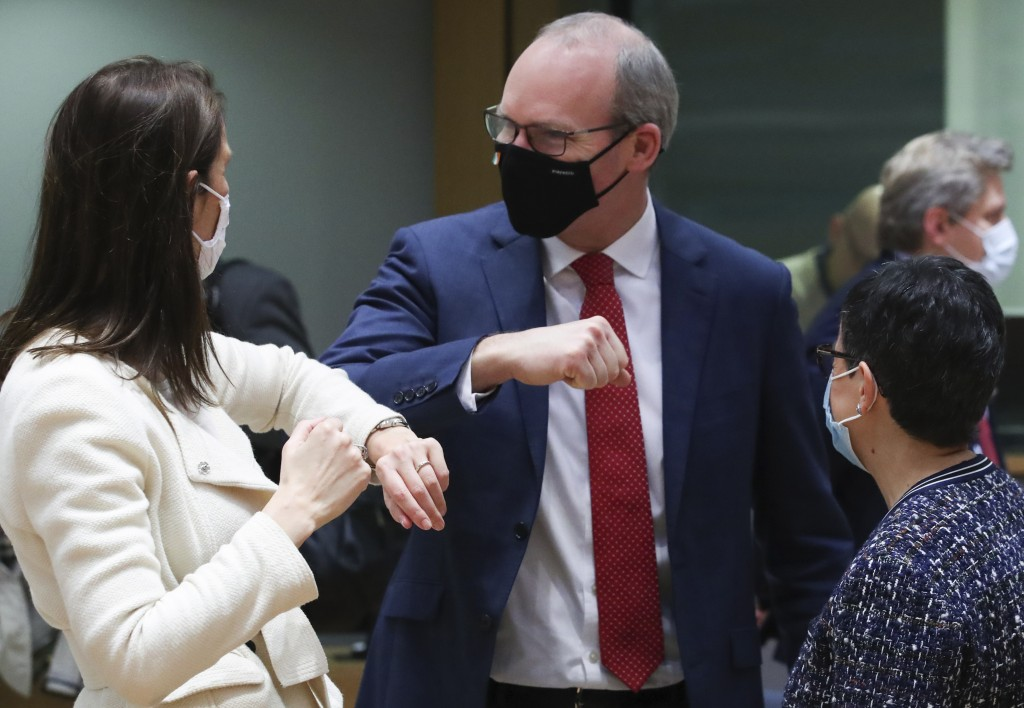 Belgium's Foreign Minister Sophie Wilmes, left, greets Ireland's Foreign Minister Simon Coveney, center, with an elbow bump during a meeting of EU for...
