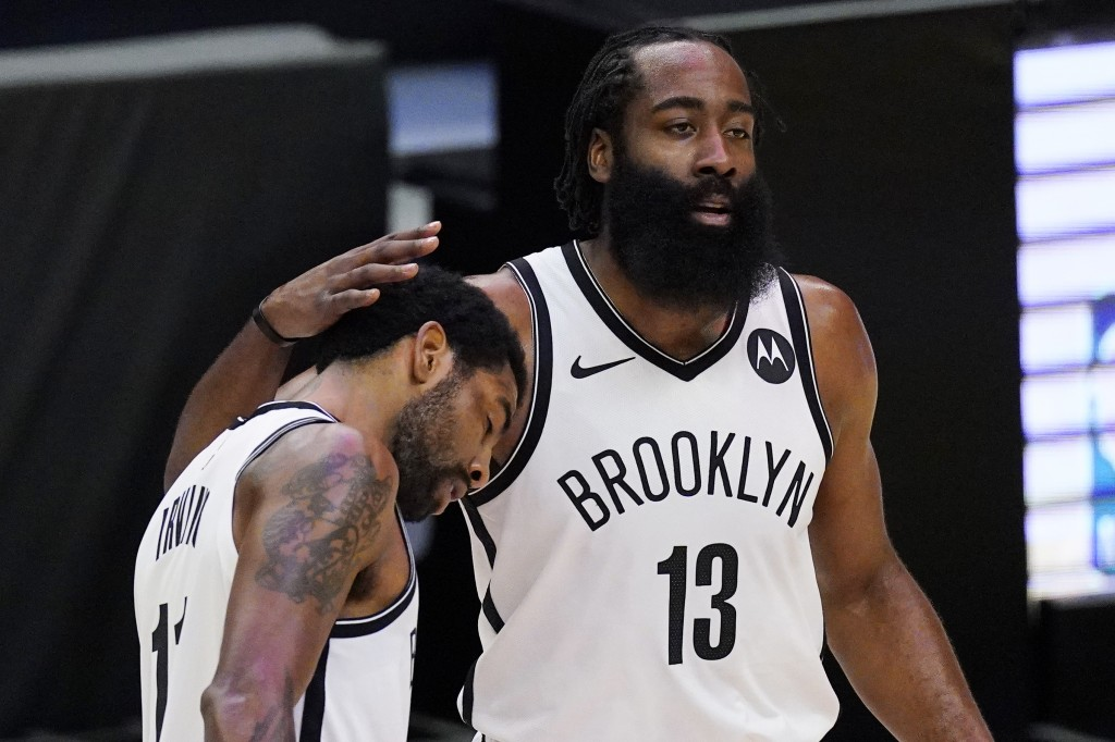 Brooklyn Nets guard Kyrie Irving, left, gets a pat on the head from guard James Harden during a timeout in the first half of the team's NBA basketball...