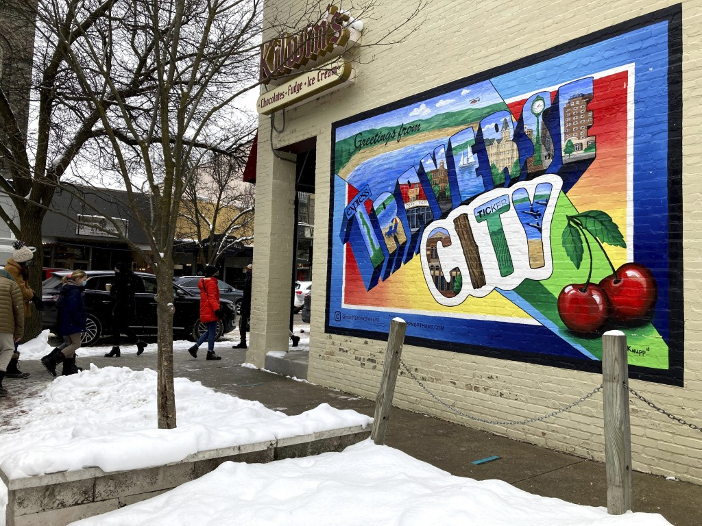 A mural adorns the wall of a chocolate shop in downtown Traverse City, Mich., Feb. 13, 2021. Controversy over a local official's display of a gun duri...