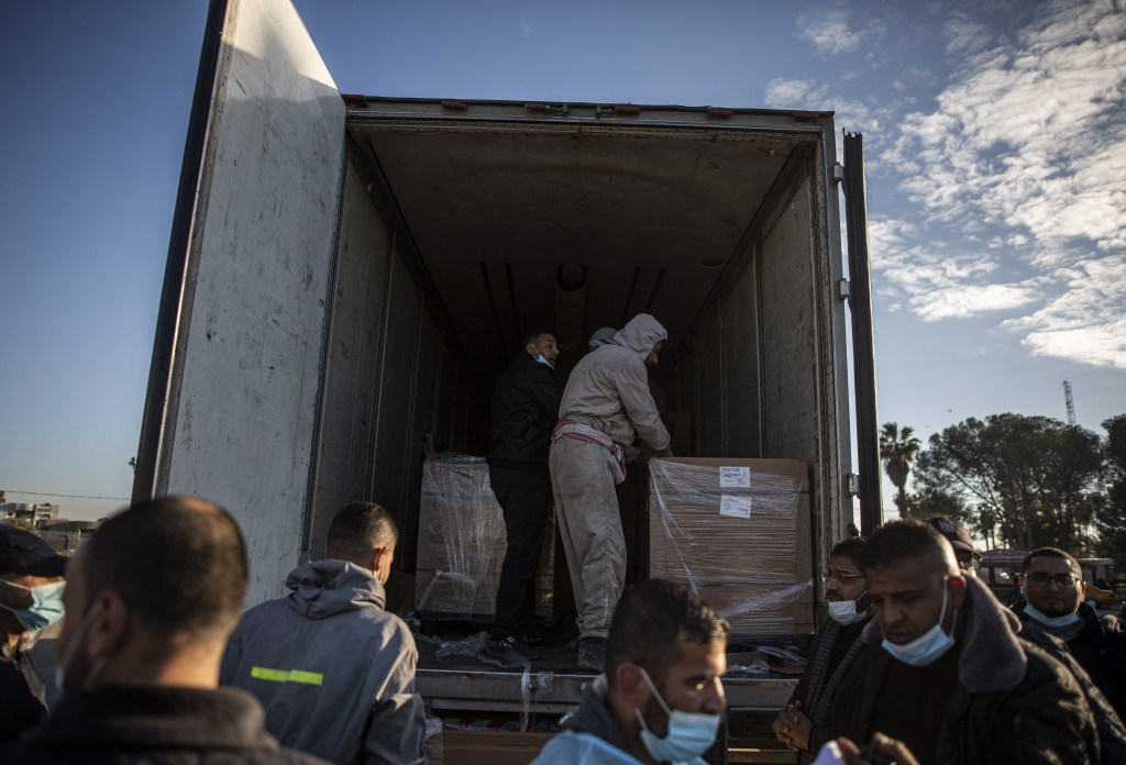 Palestinian workers unload a truck from 20,000 doses of Russian-made Sputnik V vaccine upon its arrival to Gaza Strip, at the Rafah crossing border wi...