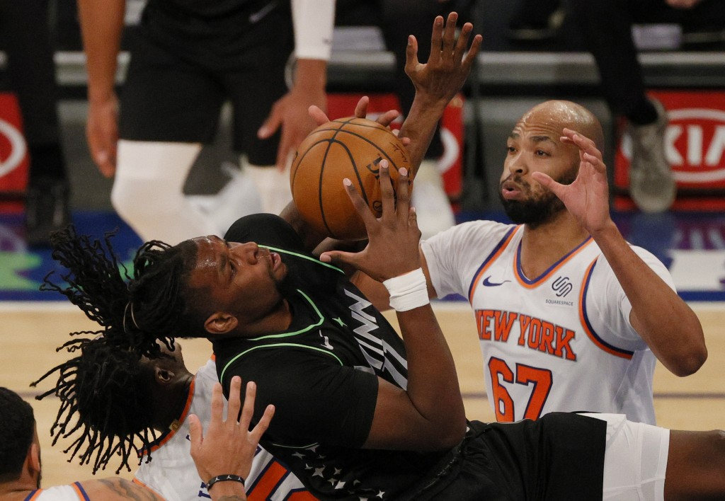 Naz Reid, left, of the Minnesota Timberwolves looks to shoot as Taj Gibson, right, of the New York Knicks defends during the first half of an NBA bask...