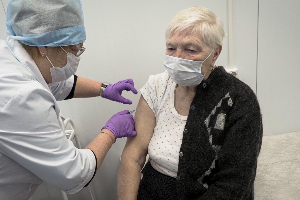 A Russian medical worker administers a shot of Russia's Sputnik V coronavirus vaccine to Galina Shilova in a local rural medical post in the village o...