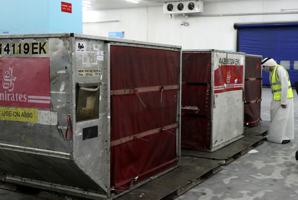 A man checks a shipment of Pfizer-BioNTech COVID-19 coronavirus vaccines after being offloaded into refrigerated storage from an Emirates Airlines Boi...