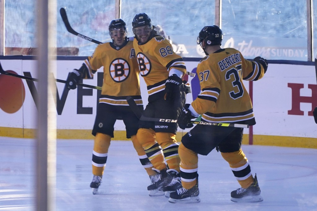 Boston Bruins right wing David Pastrnak, center, celebrates with teammates Brad Marchand, left and Patrice Bergeron after scoring against the Philadel...