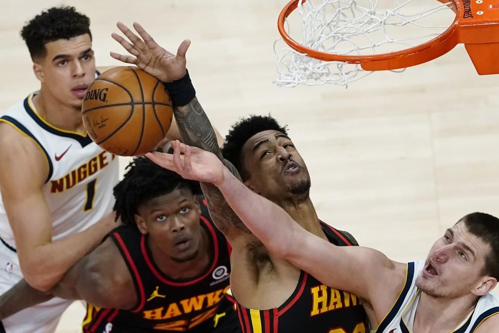Denver Nuggets center Nikola Jokic (15) battles Atlanta Hawks' John Collins (20) and Cam Reddish (22) for a rebound during the first half of an NBA ba...