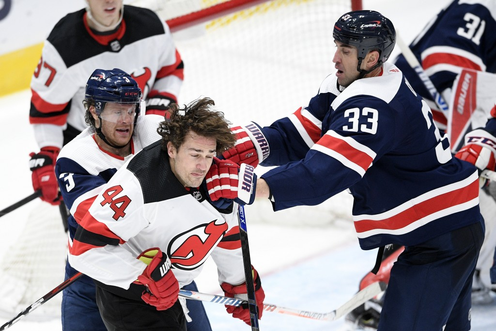 Washington Capitals defenseman Zdeno Chara (33) and defenseman Nick Jensen (3) scuffle with New Jersey Devils left wing Miles Wood (44) during the sec...